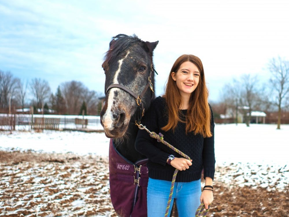 Keara and her horse, Storm, stand in the sunny, snowy fields of the Miami University equestrian center.