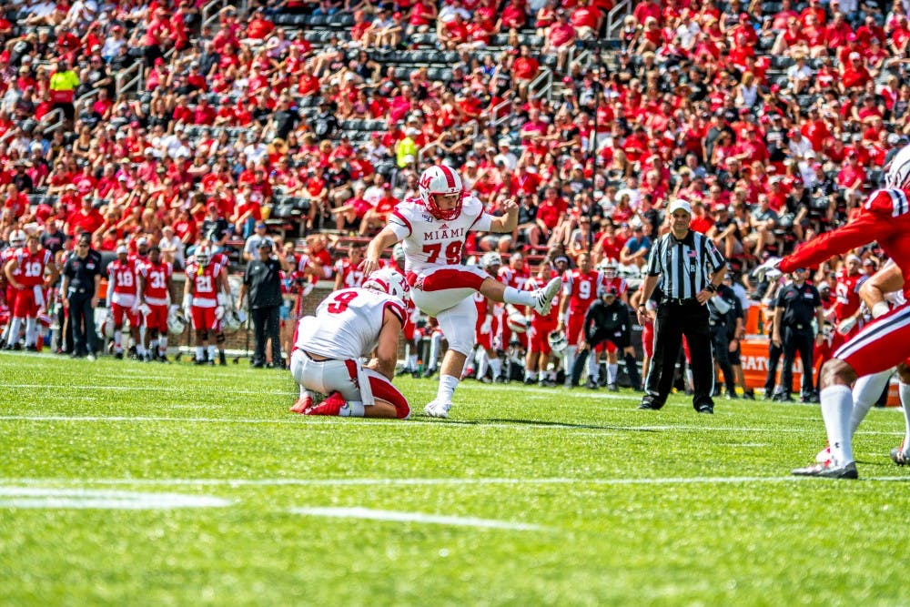 <p>Redshirt senior punter Kyle Kramer serves as the holder for a field goal by senior kicker Sam Sloman against the Cincinnati Bearcats on Sept. 14. Both players have been instrumental to the RedHawks this season.</p>