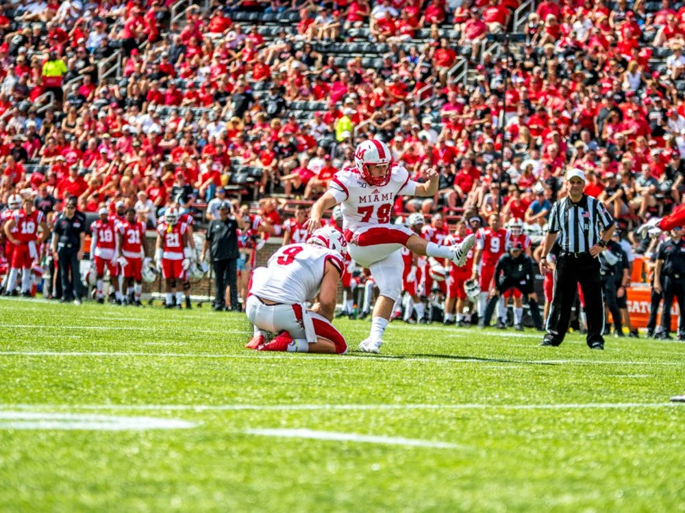 Redshirt senior punter Kyle Kramer serves as the holder for a field goal by senior kicker Sam Sloman against the Cincinnati Bearcats on Sept. 14. Both players have been instrumental to the RedHawks this season.