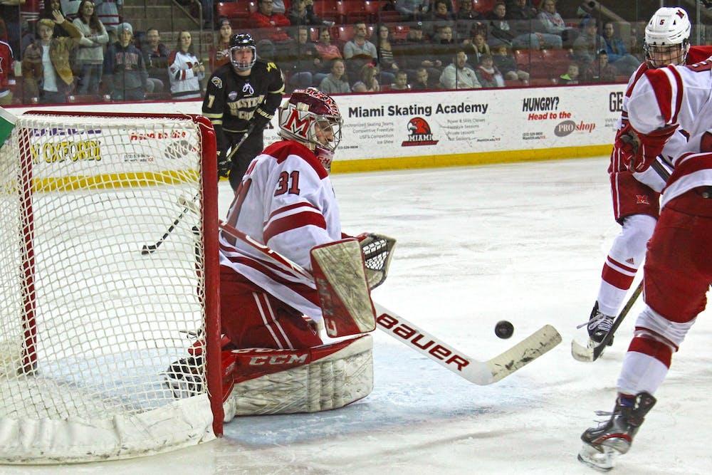 <p>Senior goaltender Ryan Larkin hurries to block a shot in a 2-2 tie against Western Michigan on Feb. 14 at the Goggin Ice Center. Larkin stopped 26 shots.</p>