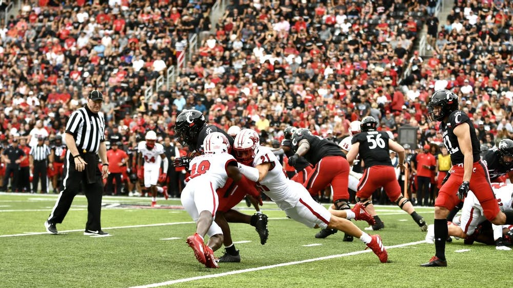 Veteran defensive backs Cedric Boswell (No. 18) and Sterling Weatherford (No. 21) combine for a tackle on a Cincinnati player. Weatherford intercepted a pass in Miami's 49-14 loss to the Bearcats.