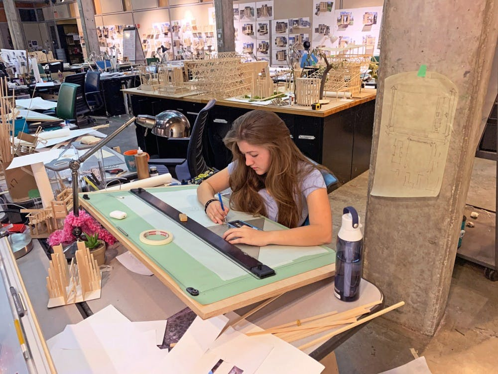 <p>First year Claire Bateson works on her architecture homework in the studio. Architecture students face over a thousand dollars of fees for supplies. </p>