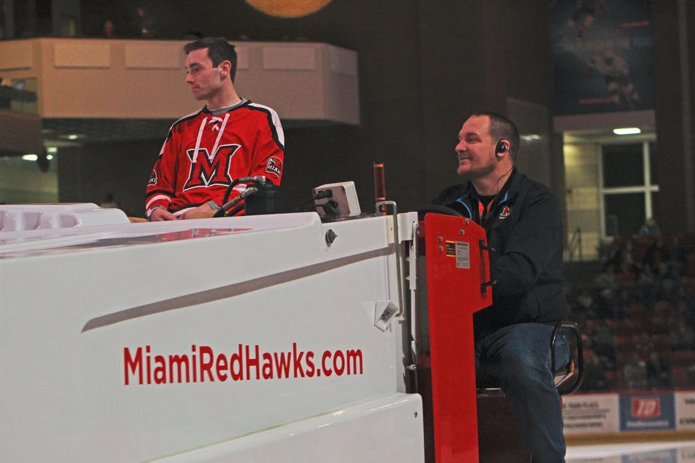<p>Brandon Hall (right) drives a Zamboni around the Steve &#x27;Coach&#x27; Cady Arena ice during a hockey game between the Miami RedHawks and the Western Michigan Broncos on Feb. 14.</p>
