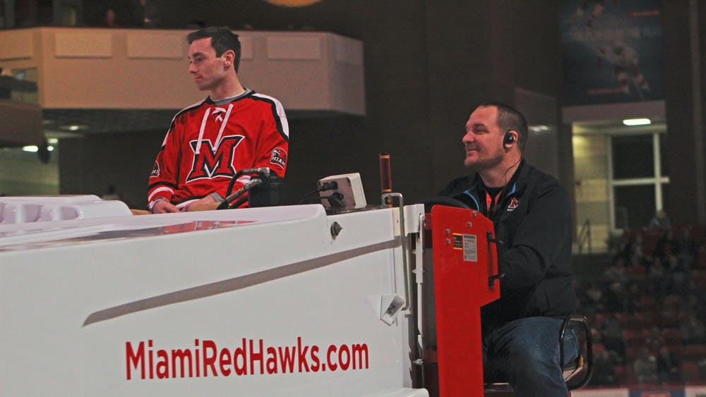 Brandon Hall (right) drives a Zamboni around the Steve 'Coach' Cady Arena ice during a hockey game between the Miami RedHawks and the Western Michigan Broncos on Feb. 14.