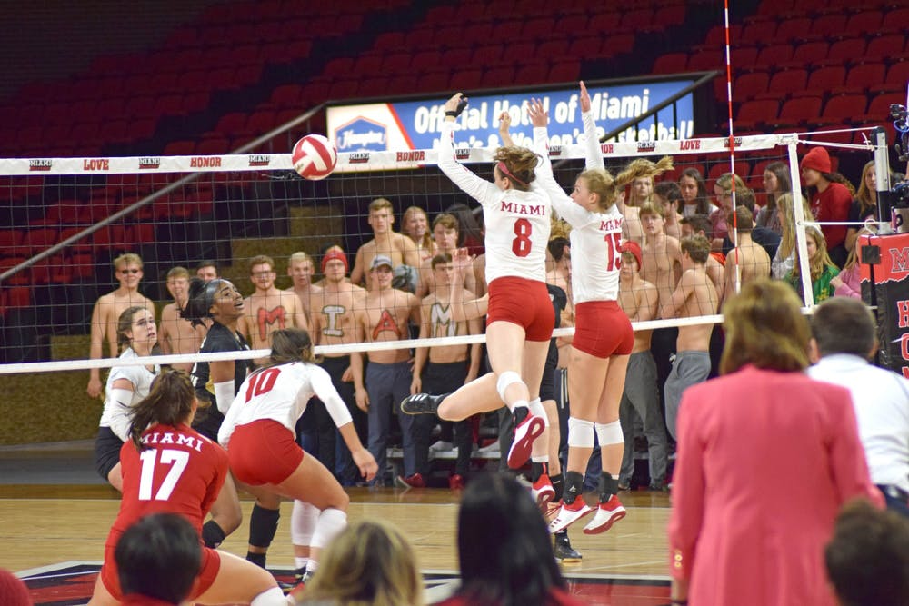 <p>Senior middle hitter Margaret Payne and freshman outside hitter Allyson Severance combine for a block against Kent State. Miami beat the Golden Flashes, 3-0, on Nov. 2 and Millett Hall.</p>