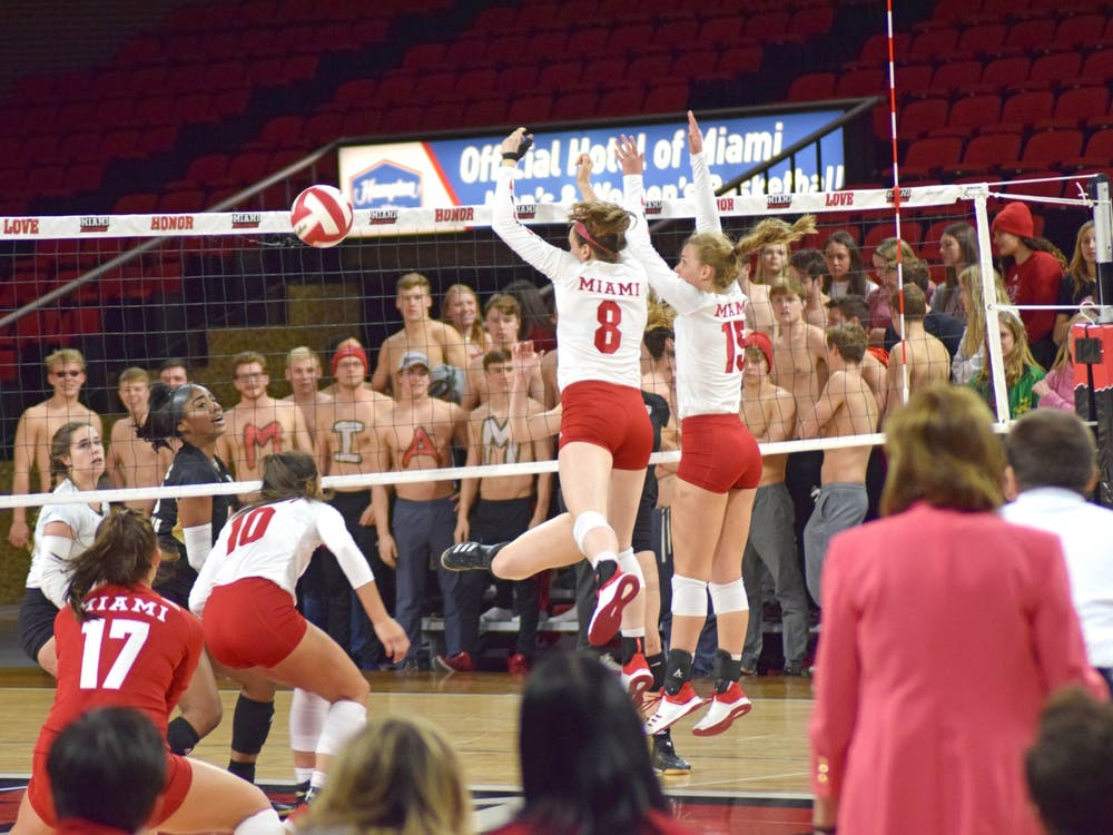 Senior middle hitter Margaret Payne and freshman outside hitter Allyson Severance combine for a block against Kent State. Miami beat the Golden Flashes, 3-0, on Nov. 2 and Millett Hall.