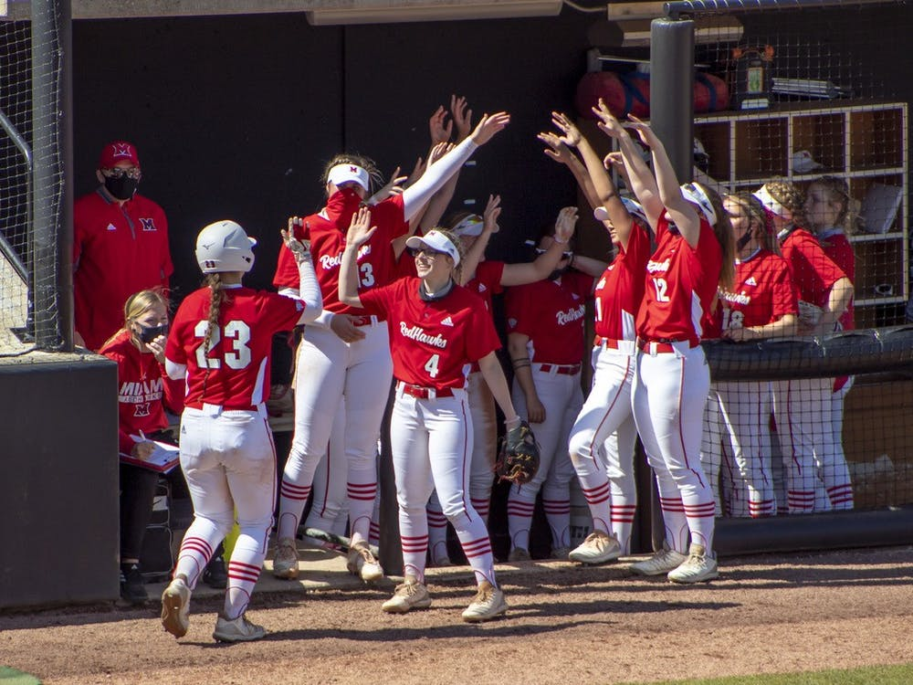 The bench celebrates after junior infielder Allie Cummins scores a run.