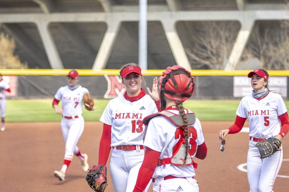 <p>Senior pitcher Courtney Vierstra high-fives junior catcher Allie Cummins during a weekend series vs Buffalo.</p>