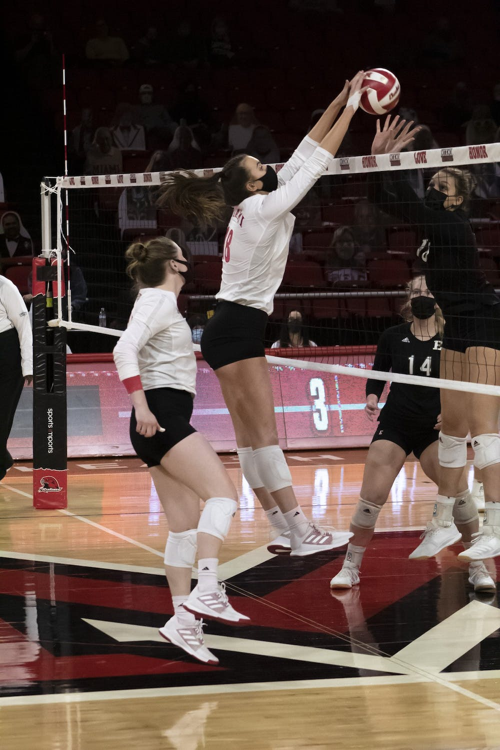<p>Senior right side Avarie Powell (pictured, middle) gets a block during a weekend series vs. Eastern Michigan.</p>