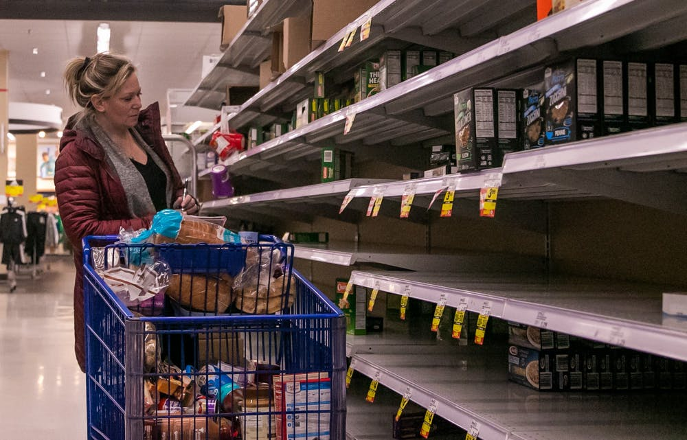 A woman looks through a sparsely stocked shelf at Meijer March 12, 2020 after MSU cancelled classes due to coronavirus.