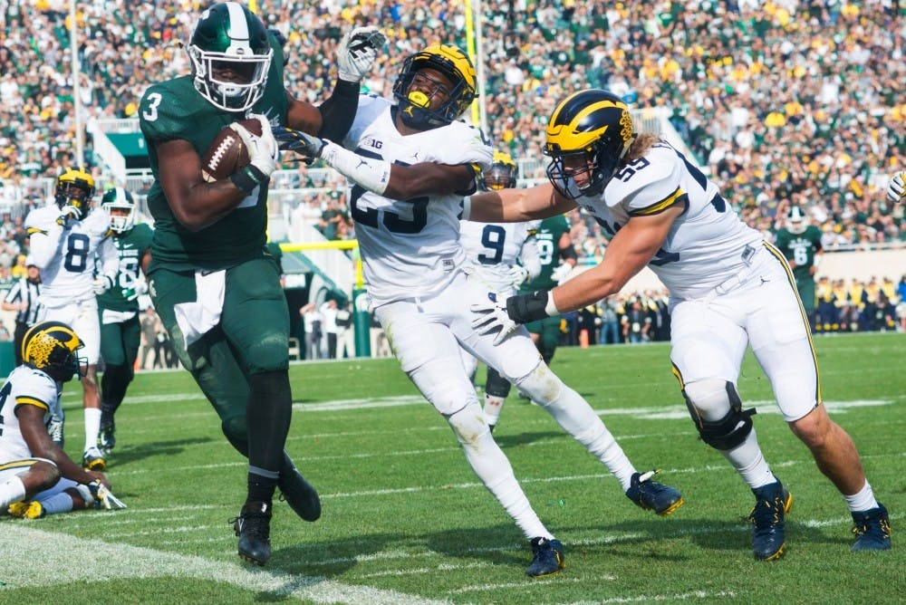 Sophomore running back L.J Scott (3) runs the ball up the field while being tackled by Michigan safety Nate Johnson (25) during the game against Michigan on Oct. 29, 2016 at Spartan Stadium. The Spartans were defeated by the Wolverines, 32-23.