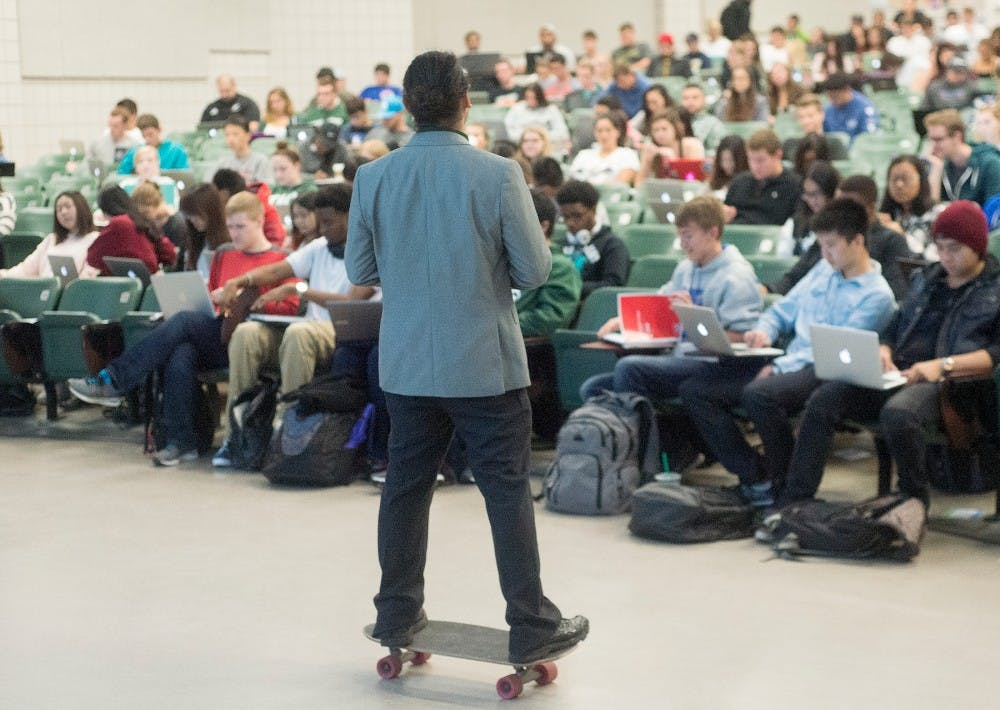 <p>Media and information assistant professor Rabindra Ratan skateboards around his classroom on Sept. 22, 2015 in Wells Hall. Ratan's class starts at 8:30 in the morning and he believes skateboarding while he teaches helps his students to stay awake and focused on the lecture.</p>