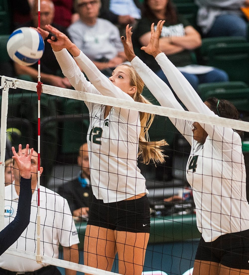 <p>Freshman setter Rachel Minarick and senior middle blocker block the ball Oct. 3, 2014, during a game against the University of Michigan at Jenison Fieldhouse. The Spartans defeated the Wolverines, 3-1. Erin Hampton/The State News</p>