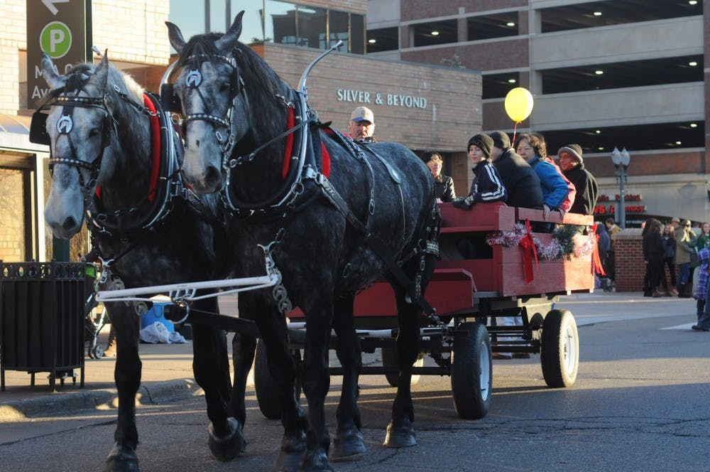 Horses trot away as they carry people on Dec. 5th, 2015 on Abbot road. The horses Mark and Scheff are Geldings from the BJG Rusty acres and they provide carriage rides for the Winter Glow event. It will be about 5 years since the horses carriage have been a part of the Winter Glow event.