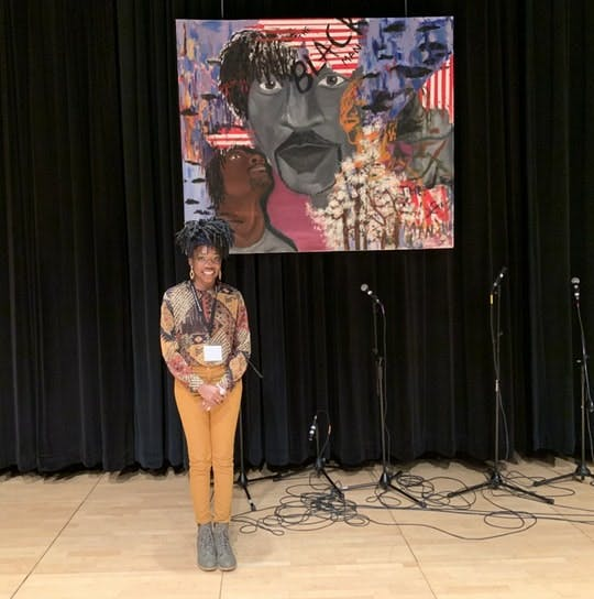 "<p>Studio Art senior Azya Moore poses next to her art piece, ""A Black Man's Dream.""&nbsp;</p>"