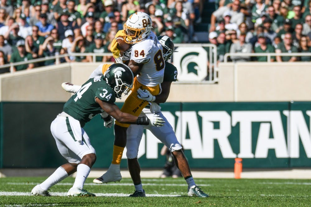 <p>Then-junior cornerback Josiah Scott (22) and then-junior linebacker Antjuan Simmons (34) tackle a Sun Devils receiver during the game against Arizona State on Sept. 14, 2019, at Spartan Stadium. The Spartans fell to the Sun Devils, 10-7.</p>