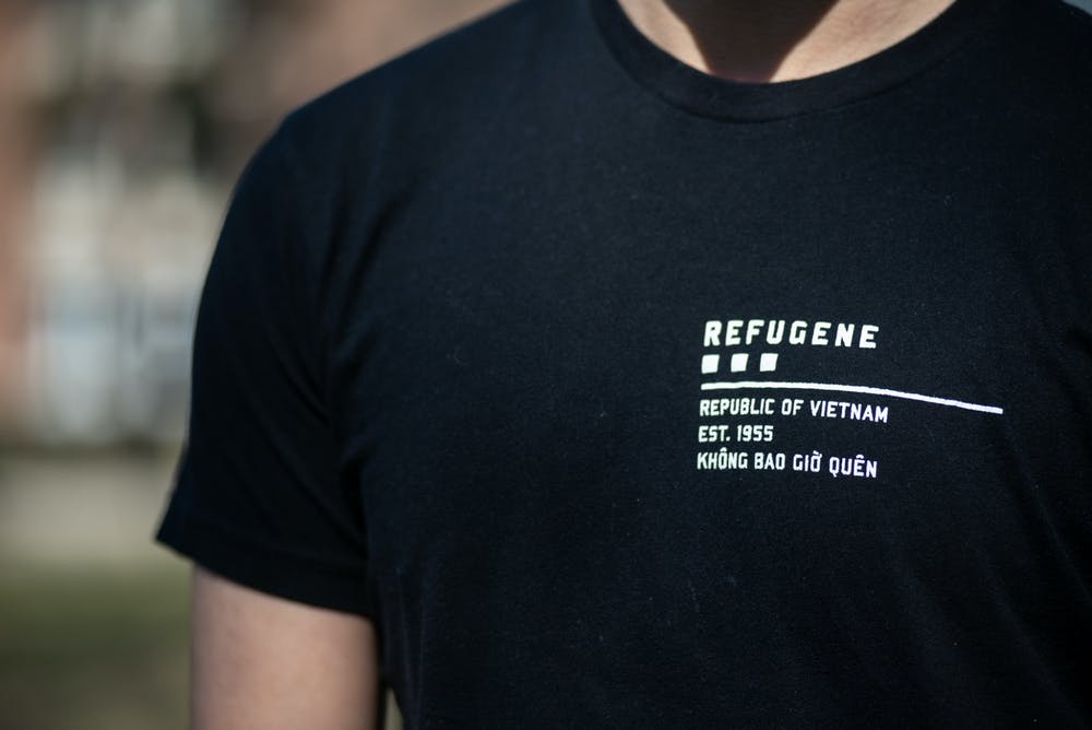 """David Tran wears a shirt with the word """"REFUGENE"""" on March 20, 2021. According to the Refugene website, """"'REFUGENE' is the extraordinary resilience in refugees—the trait we hope to pass from generation to generation. It is in our DNA, either dominant or recessive, and therein lies our mission: Find it in yourself, look for it in others, and live by it for life."""""""