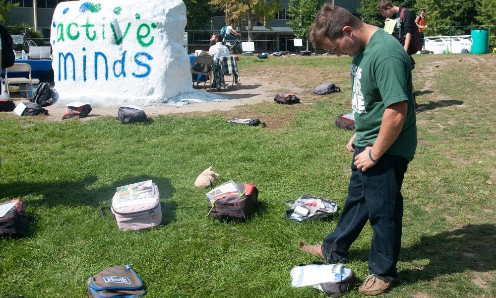 <p>Neuroscience senior and director of communications for Active Minds and Alpha Phi Omega member Bryan Meek reads a story of mental illness on Sept. 25, 2015 at the Rock on Farm Lane. Send Silence Packing was an event tailored to spread awareness about mental illnesses. Kennedy Thatch/The State News</p>