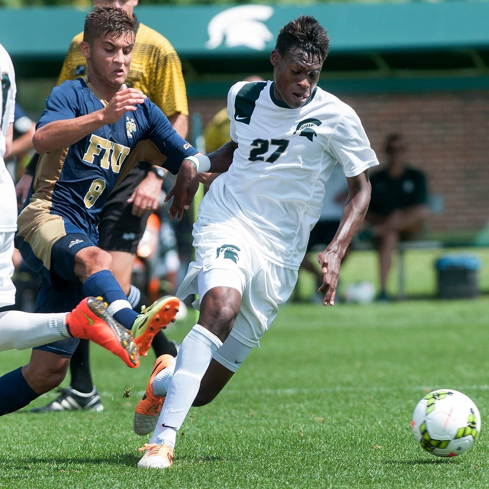 <p>Senior midfielder Fatai Alashe fights with Florida International midfielder Daniel Gonzalez for possession of the ball Aug. 31, 2014, at DeMartin Soccer Stadium at Old College Field. Raymond Williams/The State News</p>