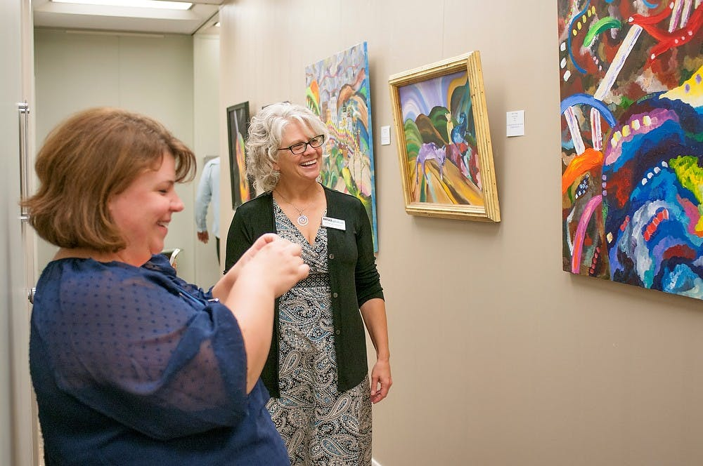 <p>Holt, Mich. resident Stacey Burley reads information about the painting on her phone, left, while Okemos, Mich. resident Dale Elshoff, right, admires it on Sept. 19, 2013, at Nisbet Building. Georgina De Moya/ The State News</p>