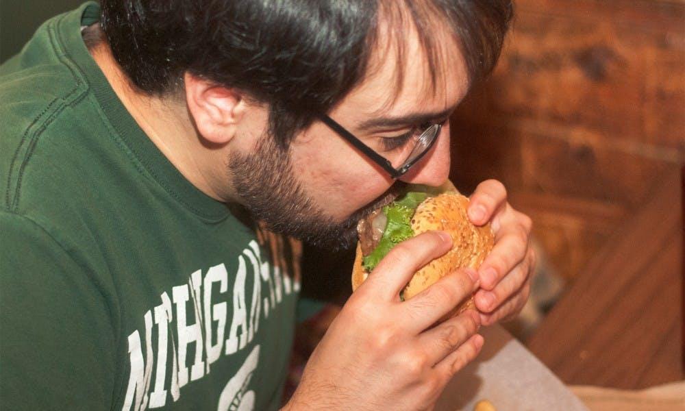 <p>Lansing resident Patrick Sandoval enjoys a burger on Sept. 3, 2014, at Crunchy's.</p>