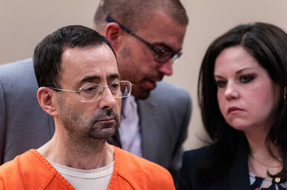 <p>Larry Nassar listens to the judge as his attorneys discuss something behind him during the plea hearing on Nov. 22, 2017, at the Veterans Memorial Court at 313 W Kalamazoo St., Lansing. Nassar pleaded guilty to seven counts.</p>