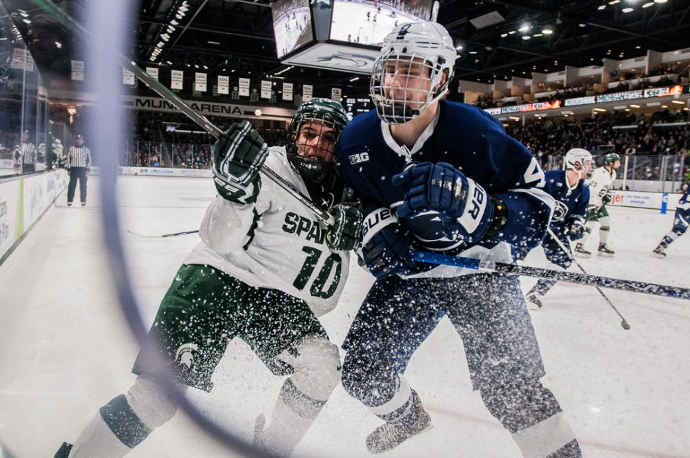 Sophomore forward Sam Saliba (10) fights for the puck with Penn State's defenseman Kris Myllari (4) during the game on Feb. 16, 2018 at Munn Ice Arena. The Spartans beat the Nittany Lions 4-2.