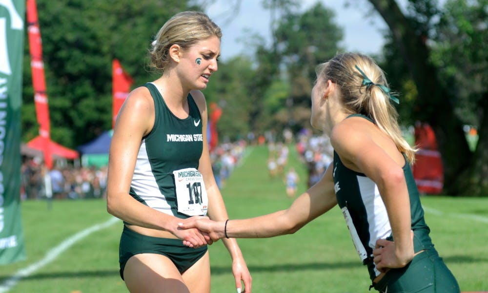 <p>Junior Rachele Schulist, left, and teammate junior Alexis Wiersma congratulate each other after the women's college 6K race Sept. 18, 2015 during the Spartan Invitational at Forest Akers Golf Course in East Lansing. Schulist's time for this race was 21:01. Wiersma's time was 21:07.</p>