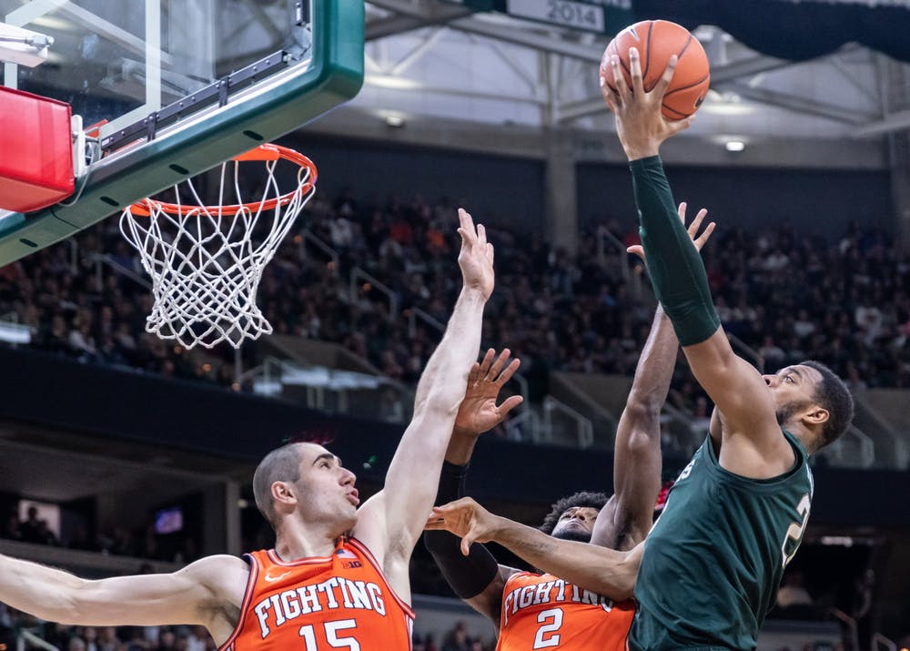 Junior forward Xavier Tillman (right) shoots over Illinois forwards Giorgi Bezhanishvili (left) and Kipper Nichols (2). The Spartans defeated the Illini, 76-56, at the Breslin Student Events Center on January 2, 2020.
