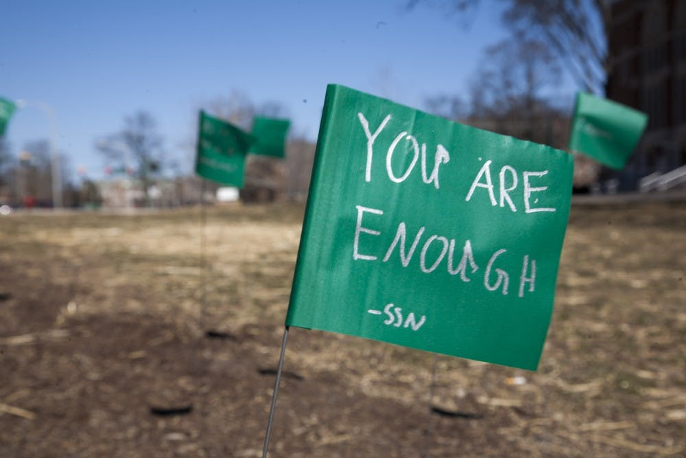 <p>Green flags with motivational messages written by students as part of the Green Flag Challenge on March 19, 2018, at The Rock on Farm Lane. (Charles Benoit | State News)</p>