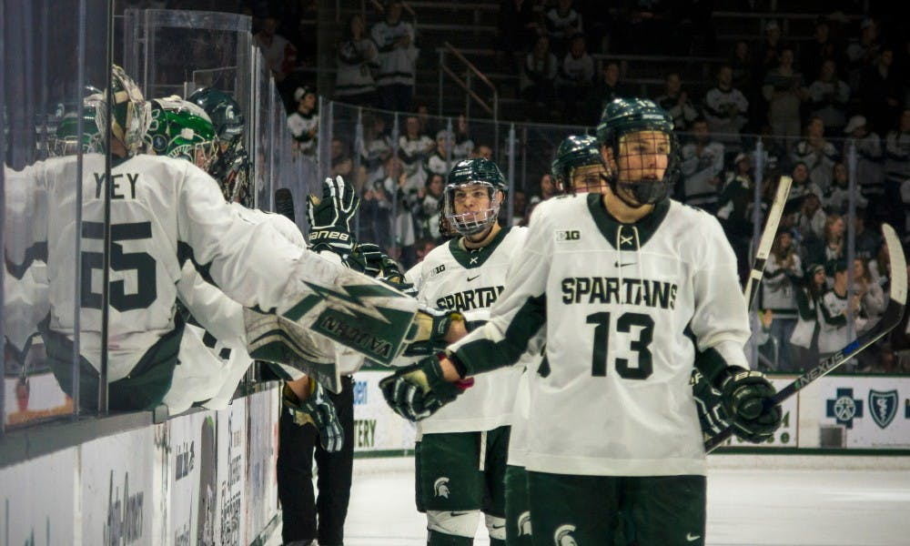 The Spartans congratulate each other after scoring a goal during the game against Ohio State on Feb. 17, 2017 at Munn Arena. The Spartans were defeated by the buckeyes, 3-2.