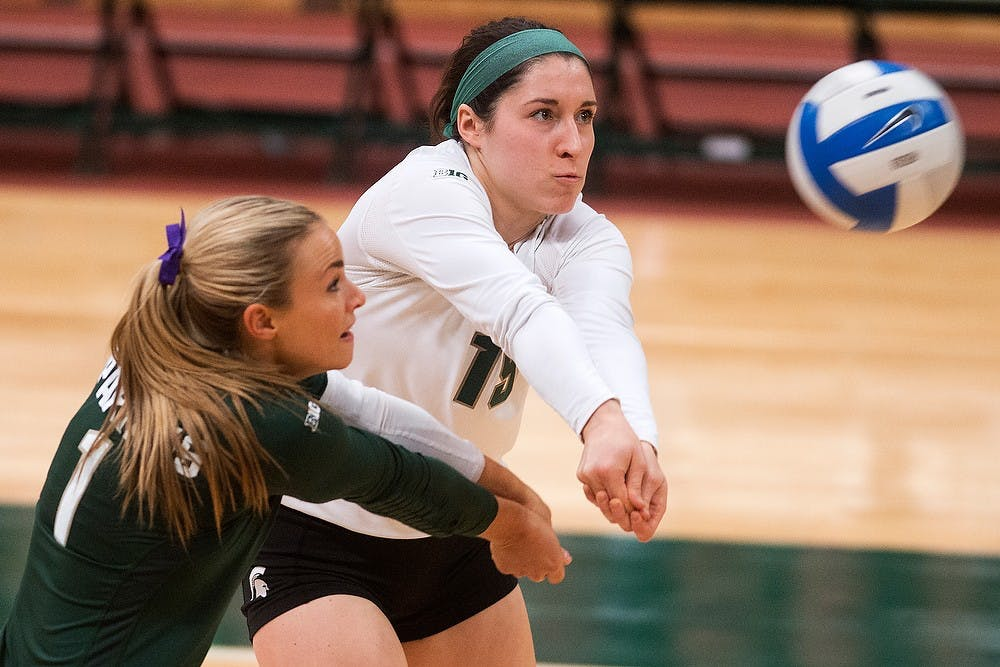 <p>Freshman defensive specialist Marissa Ratzenberger and senior libero Kori Moster go for the ball Oct. 31, 2014, at Jenison Field House during the game against Illinois. The Spartans lost, 3-1. Julia Nagy/The State News</p>