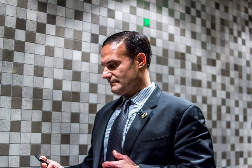 <p>Board member Brian Mosallam checks his phone before the town meeting on Feb. 1, 2018 at Kellogg Center. The town hall brought together students, staff and members of the MSU community to discuss the current climate of the campus.&nbsp;</p>