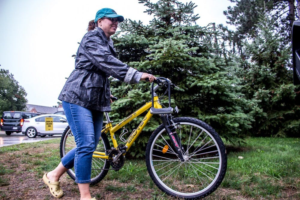 <p>Kalamazoo resident Joy Hess moves a bike on Aug. 26, 2018 in front of Williams Hall. Thousands of first-year students moved onto campus during the university's official move-in day.</p>