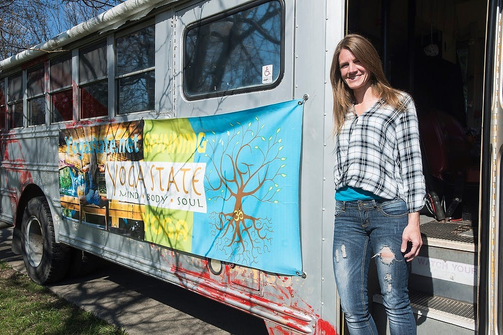 <p>Owner of Yoga State Jen Hayes poses at the door of her Yoga Bus April 28, 2015, at her home on e. Lake Lansing Rd. in East Lansing. Hayes drives the bus all around East Lansing promoting her business by giving people rides and passing around flyers. Erin Hampton</p>