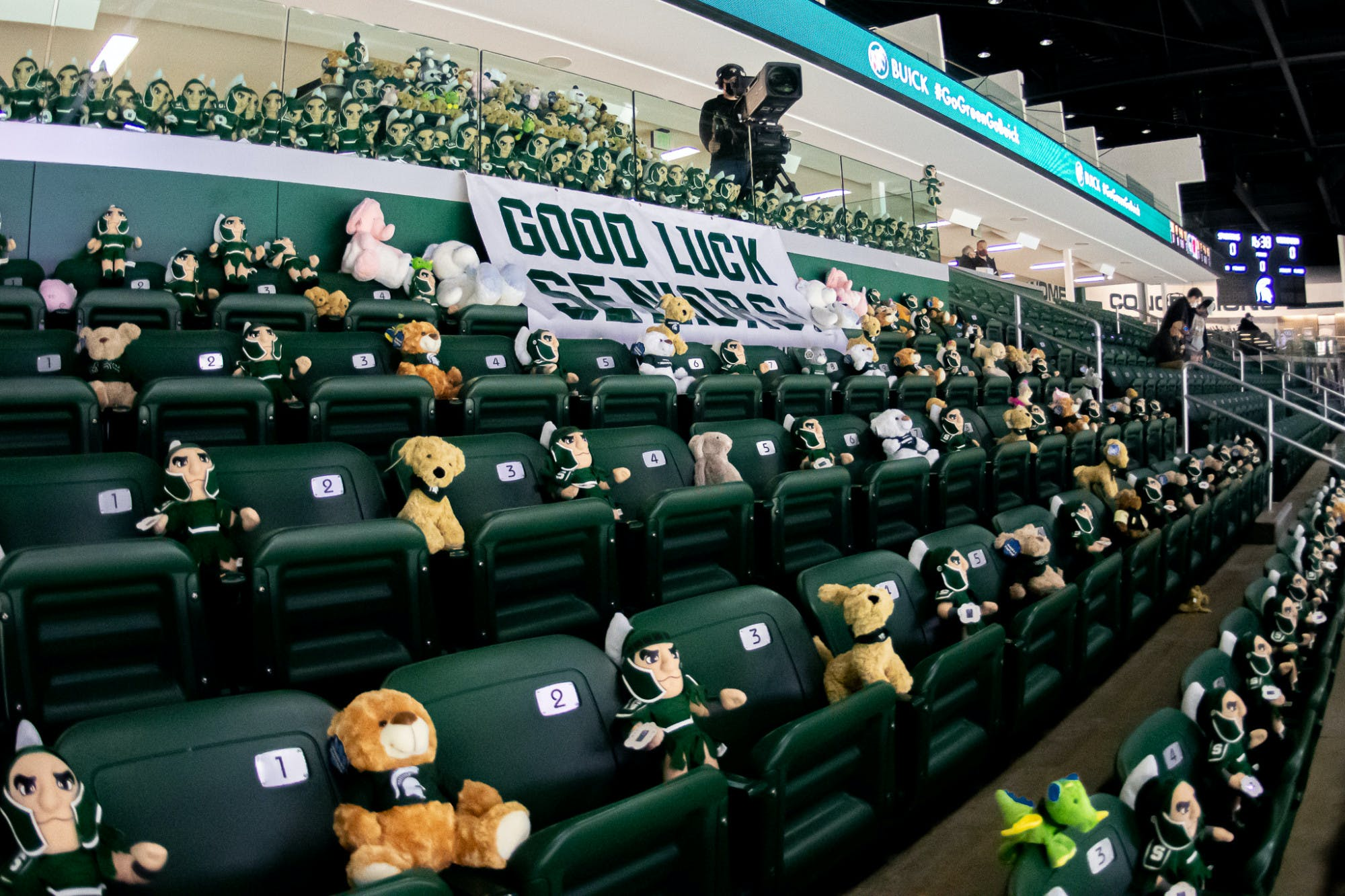 Empty sports stands are filled with stuffed animals. A sign that reads 'Good luck seniors' hangs nearby.