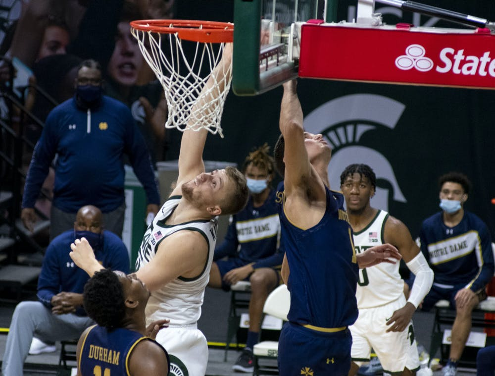 <p>Junior forward Thomas Kithier (15) scores for Michigan State in the first half of the game. Michigan State triumphed over Notre Dame, 80-70, on Nov. 28, 2020. </p>