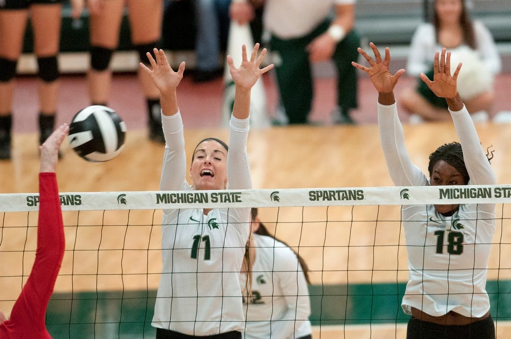 <p>Freshman outside hitter Chloe Reinig and senior middle blocker Alexis Mathews, 18, go up to block Nov. 1, 2013, during the game against Ohio State at Jenison Field House. The Spartans defeated the Buckeyes, 3-0. Julia Nagy/The State News </p>