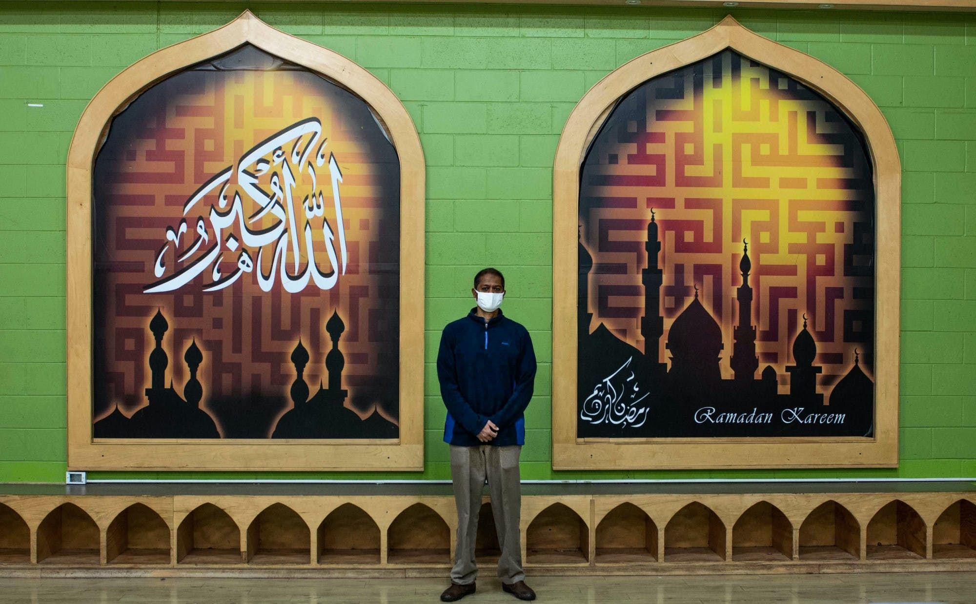 A man wearing a face mask stands for a portrait in front of a mural at an Islamic center.
