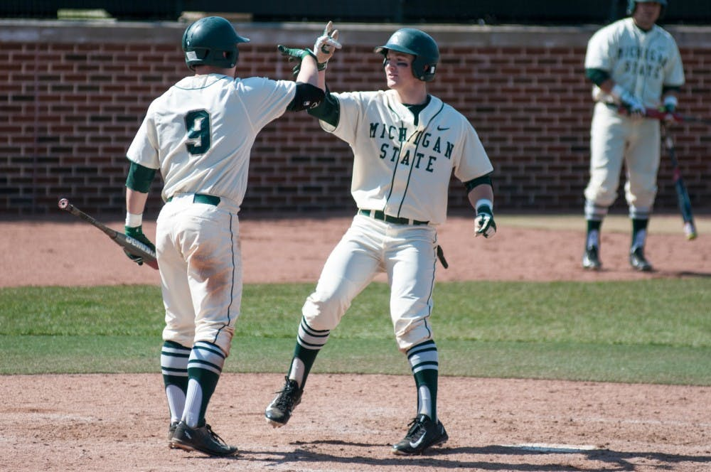 Freshman infielder Marty Bechina, right, and junior infielder Dan Durkin celebrate at home plate during the game against Rutgers on March 27, 2016 at McLane Stadium. The Spartans defeated the Scarlet Knights, 6-5.