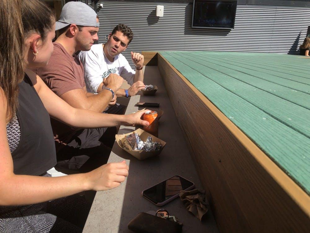 <p>Alexandra Gormely, Tate Macodnald and Zach Tearson enjoy tacos from Barrio at the taste testing for Landmark residents.</p>