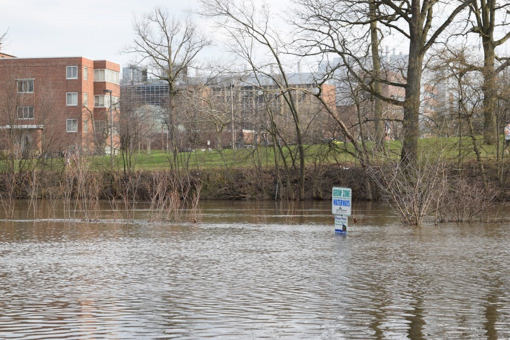 <p>Flooding engulfs a sign along the river trail that runs past Shaw Hall and under Farm Lane on April 9, 2017.</p>