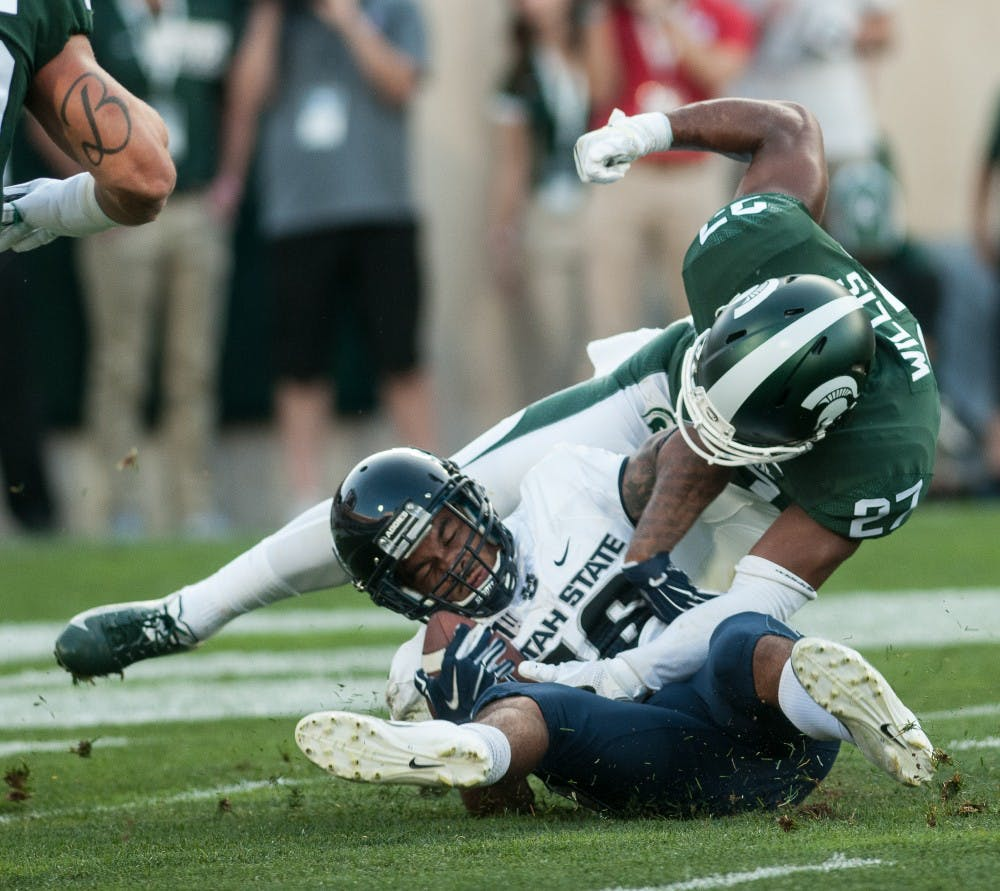 Senior defensive back Khari WIllis (27) attempts to strip the ball out of the receivers hand after making a tackle during the game against Utah State on Aug. 31, 2018 at Spartan Stadium. The Spartans defeated the Aggies 38-31.