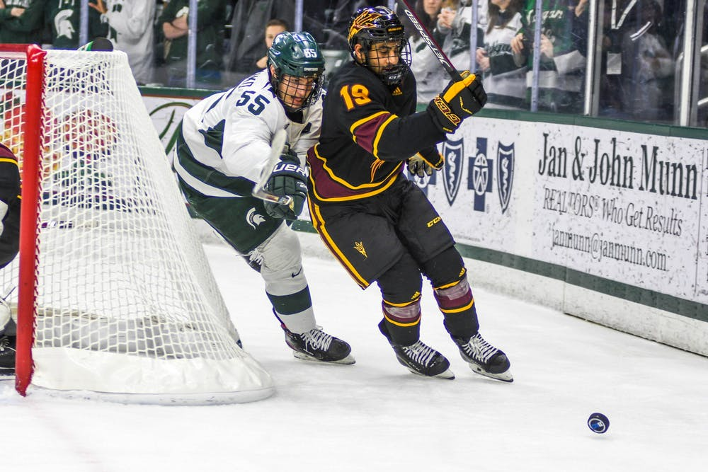 Senior center Patrick Khodorenko (55) fights for the puck during the game against Arizona at the Munn Ice Arena on Dec. 14, 2019. The Sun Devils defeated the Spartans, 4-3.