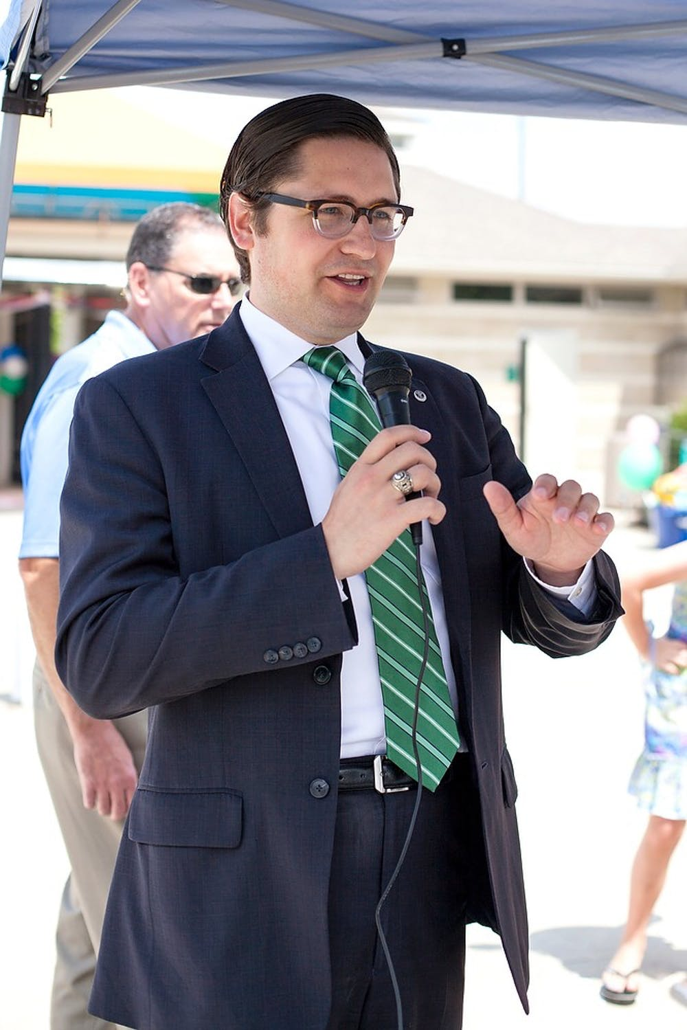 <p>East Lansing Mayor Nathan Triplett makes a speech during the 2014 Summer Splash event, July 30, 2014, at the East Lansing Family Aquatic Center. Activities at the event included a sand castle building contest, a belly flop contest and a balloon toss. Corey Damocles/The State News</p>