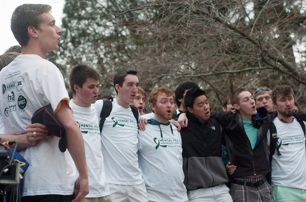 <p>The MSU Men's Glee Club performs the fight song April 10, 2014, at Beaumont Tower for Mental Health Awareness Week. Attendees heard from speakers about mental health stigmas. Meagan Beck/The State News</p>