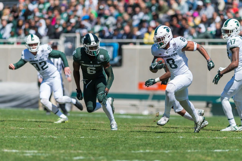 Sophomore wide receiver Jalen Nailor (8) runs from senior safety David Dowell (6). The green team beat the white team, 42-26, in the MSU Spring football game at Spartan Stadium on April 13, 2019.