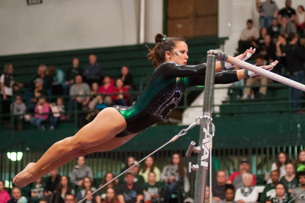 Freshman Drew Hendershot  preforms on the bars during the  MSU womens gymnastic's meet against Illinois on Feb. 19, 2016 at Jenison Field House.