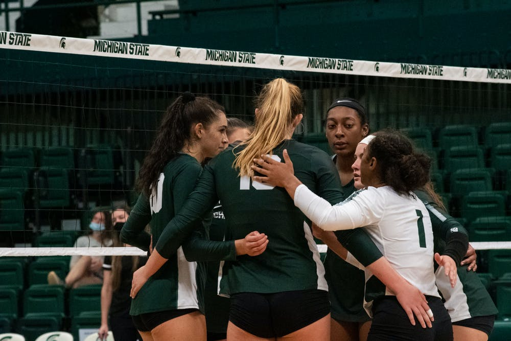 <p>Michigan State Volleyball teams join in a huddle during their game against IUPUI on Sept.18, 2021. </p>