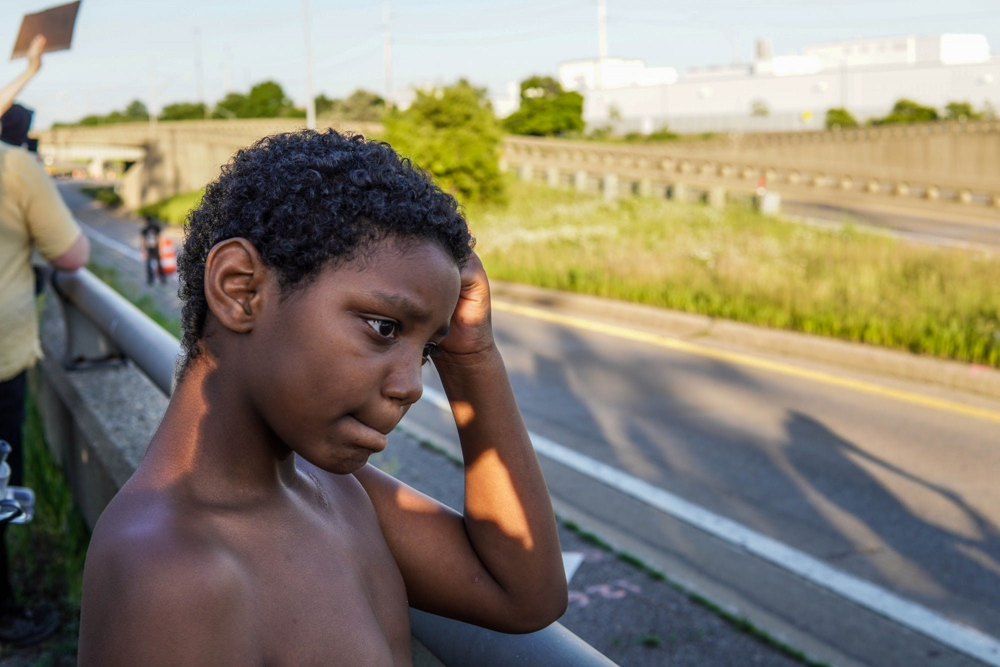 A young child rests his head on his arm, his arm on a railing that looks over a road.